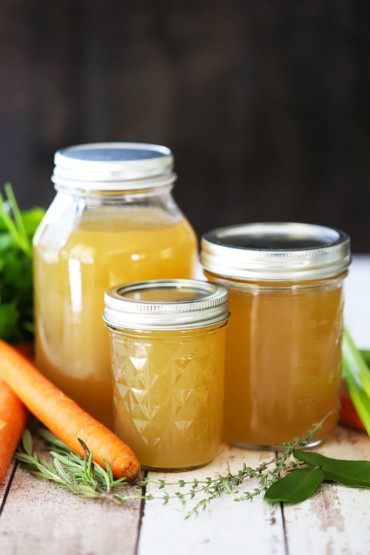 Three jars, ranging in size from small to large, filled with homemade chicken broth with loose carrots and herbs nearby.