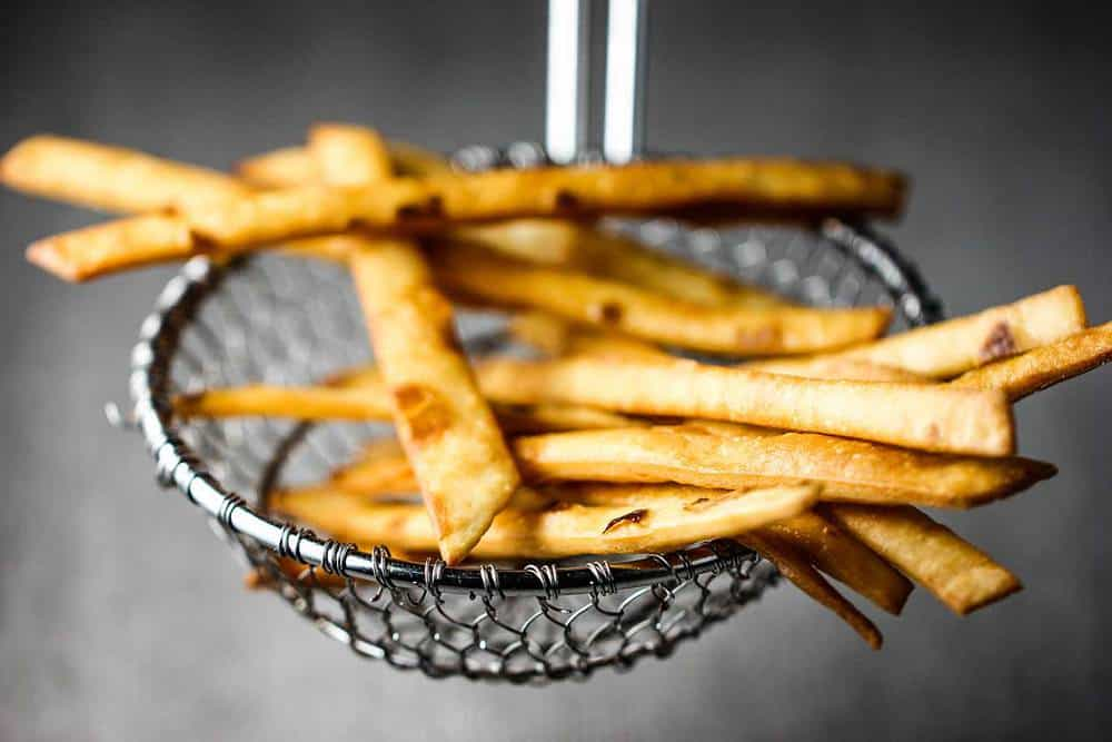 A slotted spoon holding a batch of fried flour tortilla strips.