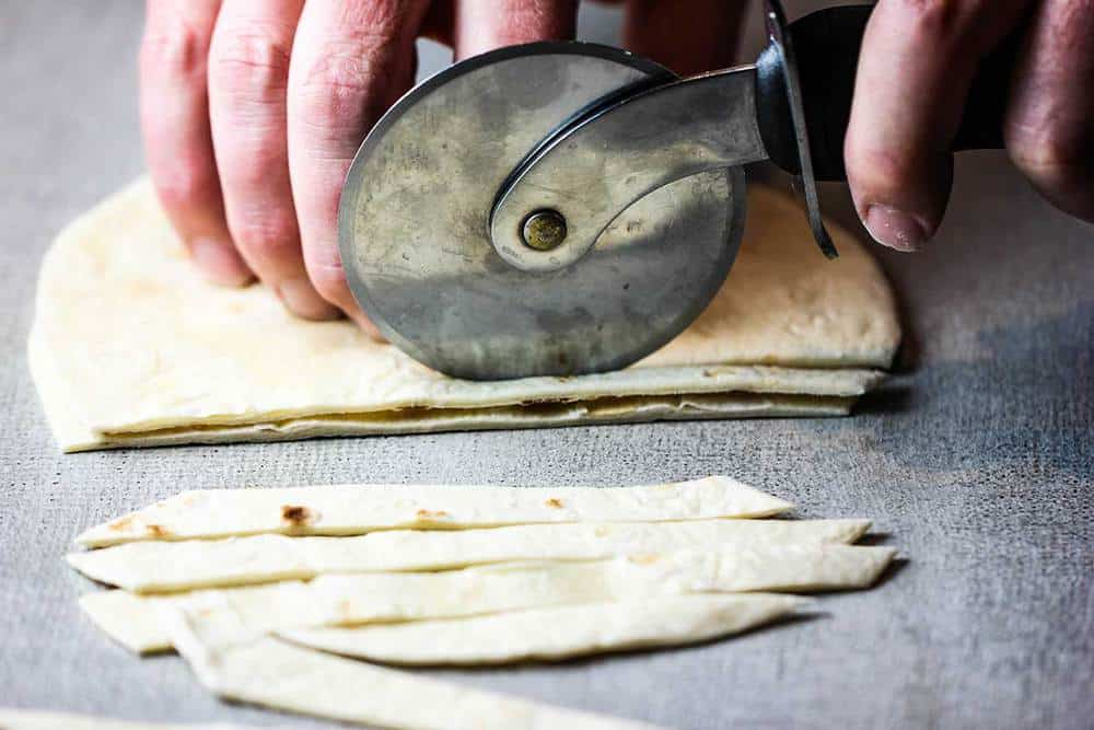 A hand using a pizza cutter to cut tortillas strips for white chili