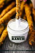 The tip of a fried asparagus being dipped into a small jar of homemade ranch dressing.