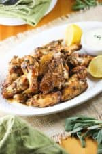 Italian Style Chicken wings on a white plate with lemon and dipping sauce