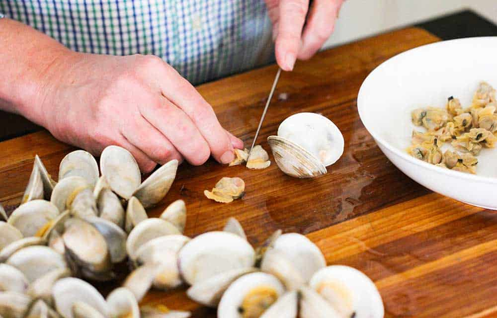 Two hands chopping clam meat on a cutting board next to opened clams.