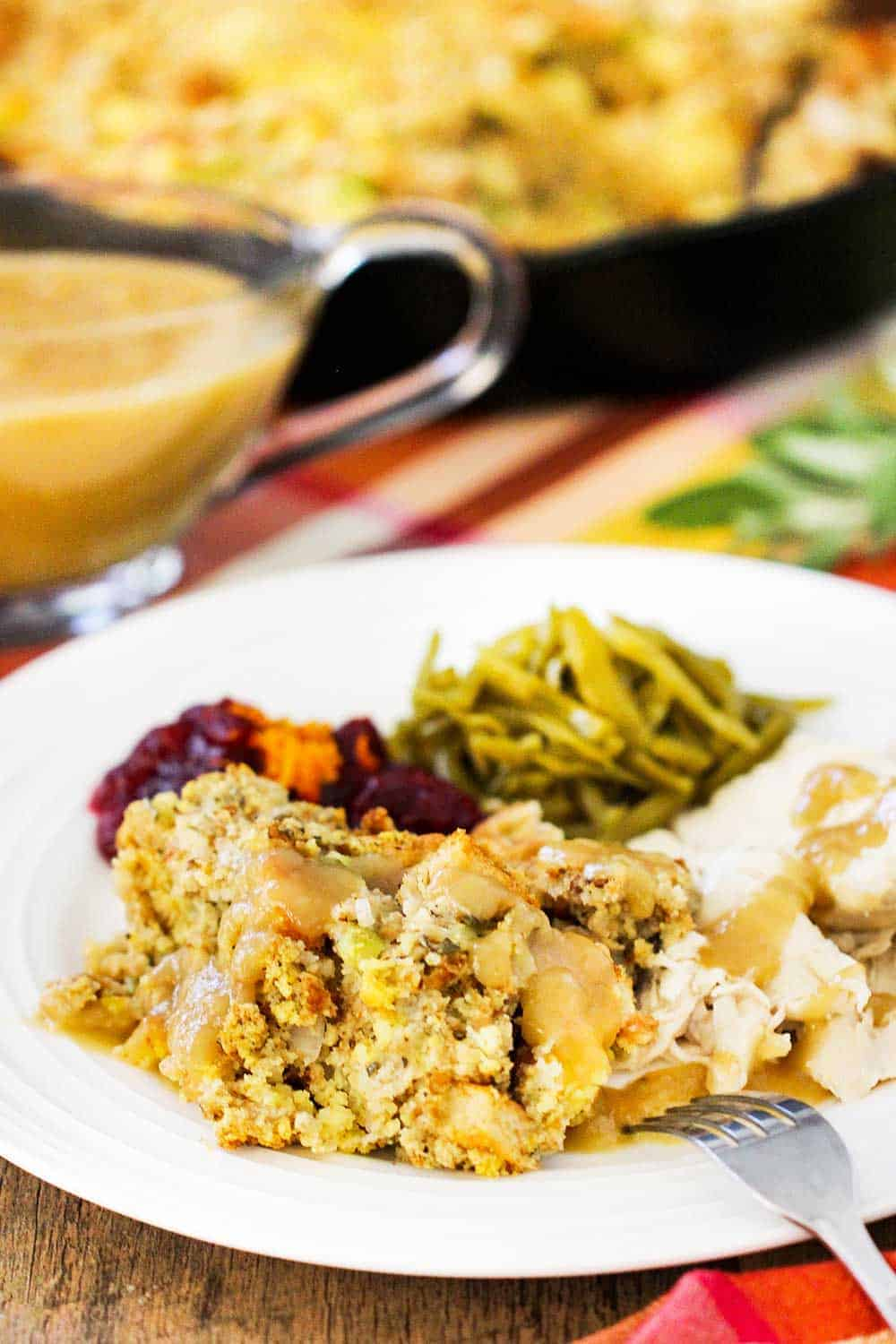 A white plate of Thanksgiving dressing, turkey, green beans, next to gravy and a black skillet.