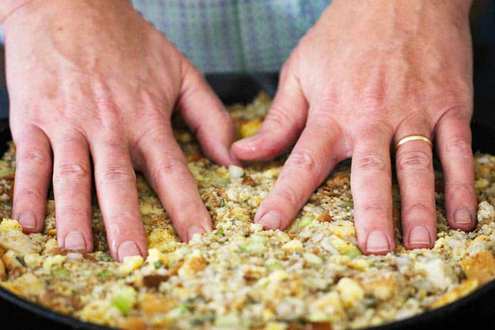 Two hands pressing onto a pan full of Thanksgiving dressing.