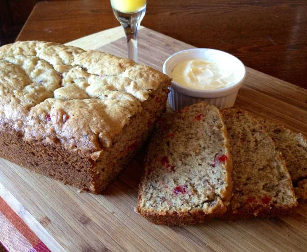 Sliced Banana Nut Bread with butter on a wooden cutting board with a glass of Champagne next to it.