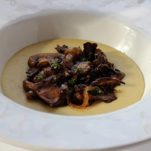 Polenta with sauteed mushrooms and caramelized onions in a white bowl