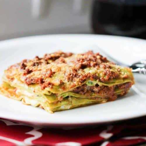 A serving of Rustic Bolognese Lasagna on a white plate on top of a red patterned place setting