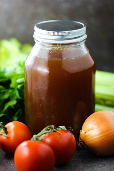 Homemade beef stock in a jar surrounded by tomatoes, celery, and other vegetables.