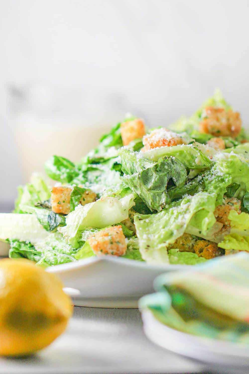 A white plate holding a classic Caesar salad with a lemon nearby.