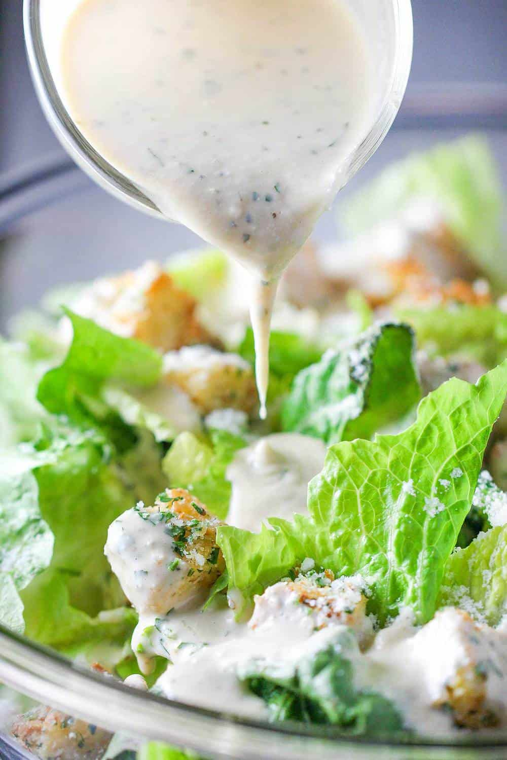 A small pitcher pouring dressing onto a classic Caesar salad.