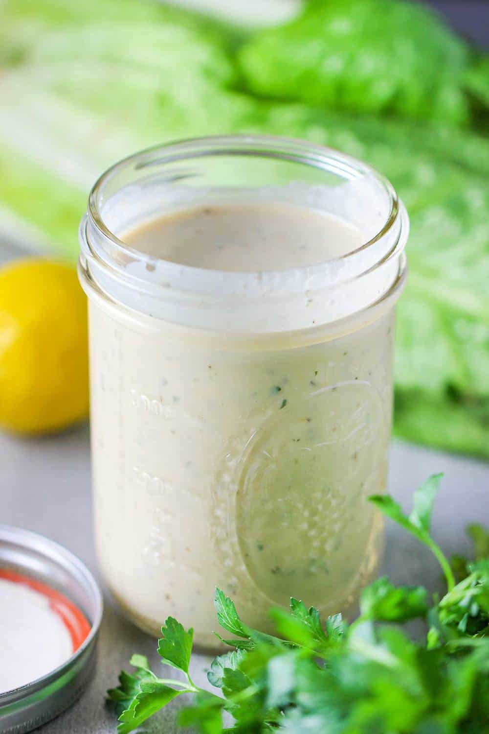 A mason jar holding Caesar dressing with lettuce and a lemon nearby.
