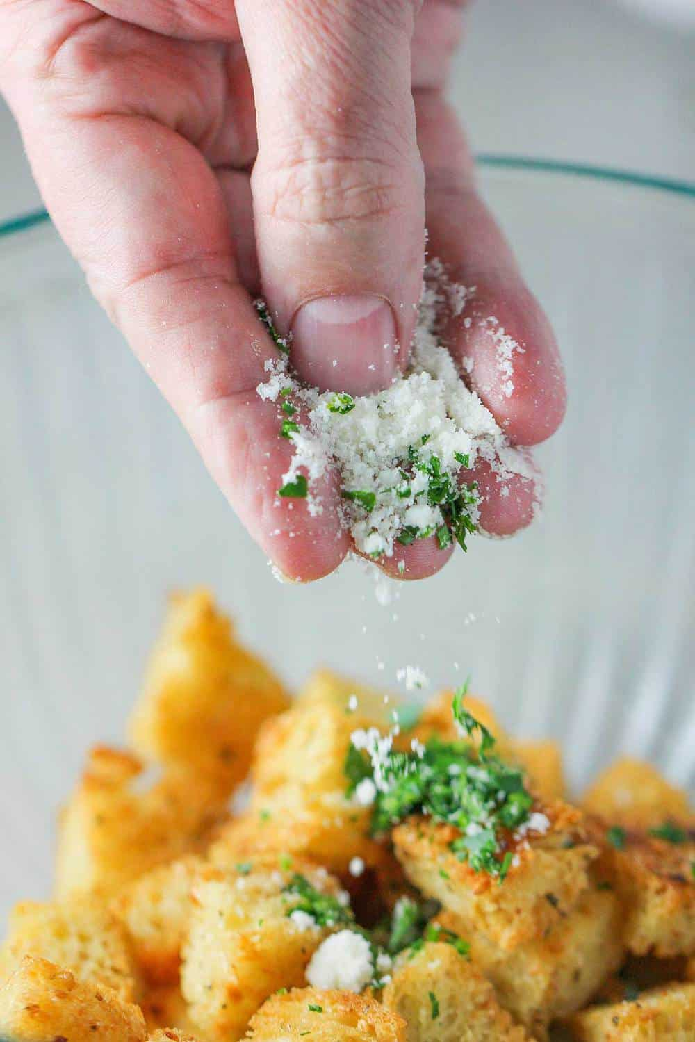 A hand sprinkling cheese and herbs onto baked croutons.