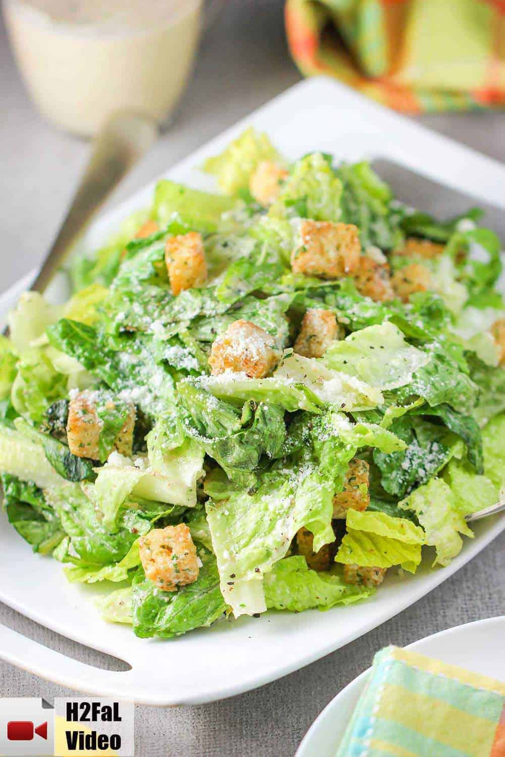 A large Caesar salad on a white plate with a colorful napkin nearby.
