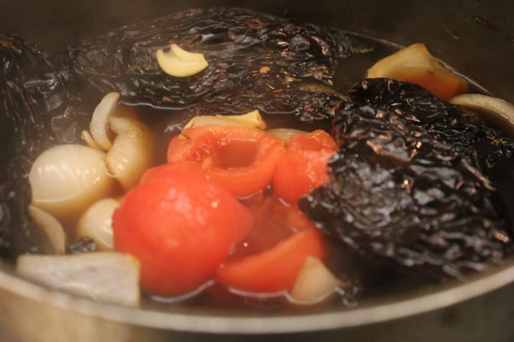 ancho chilies simmering for red enchilada sauce