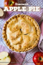 An overhead view of a homemade apple pie next to cut apples on a checkered place mat.