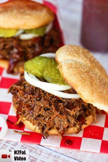 Two BBQ brisket sandwiches dripping with BBQ sauce.