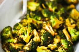 Roasted broccoli with red pepper flakes in an oval white serving platter with a silver spoon inserted into the dish.