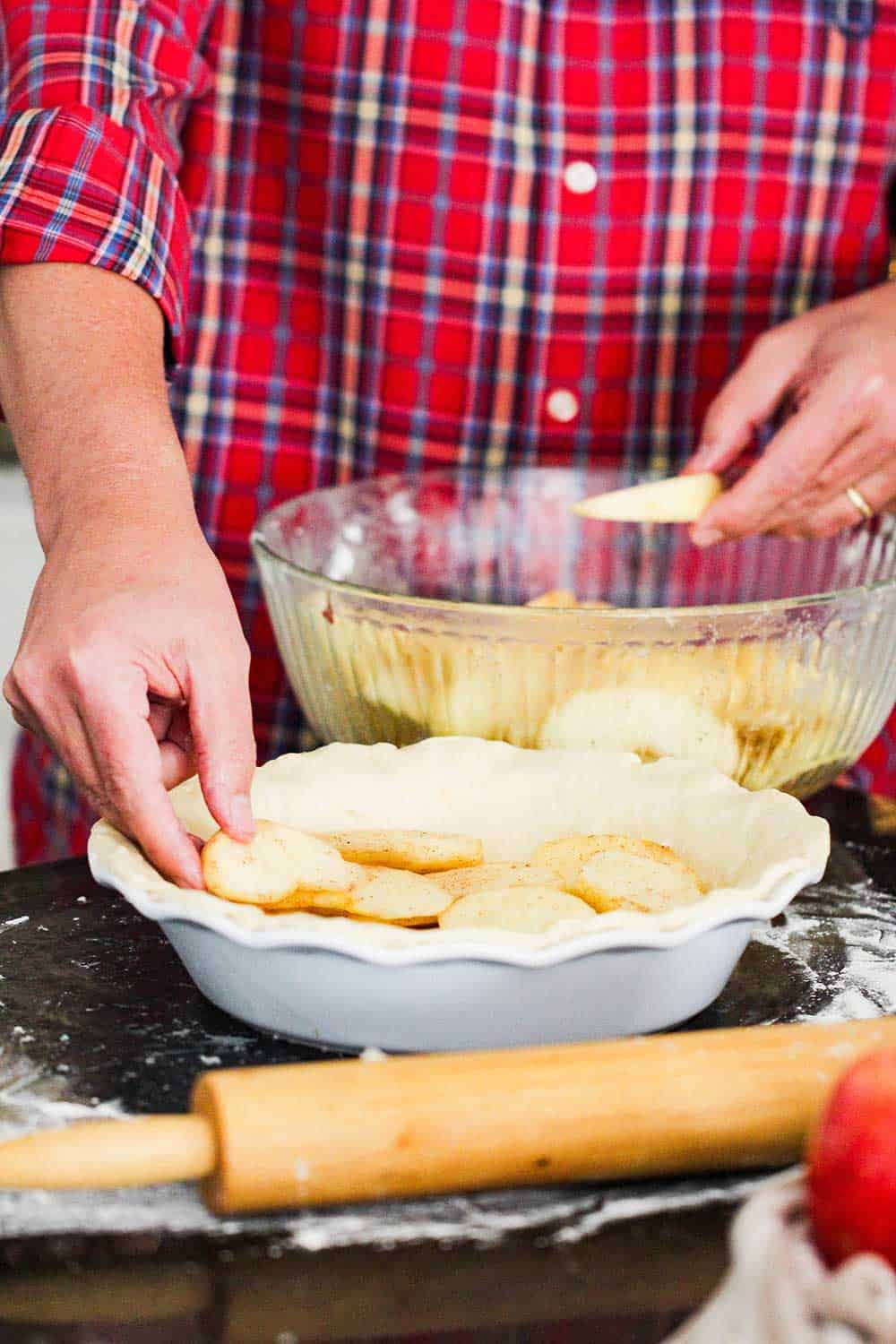 A hand layering spiced apple slices into a pie dish lined with homemade pie dough.