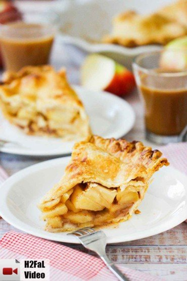 A slice of homemade apple pie on a white plate with a fork and another plate of pie behind it.