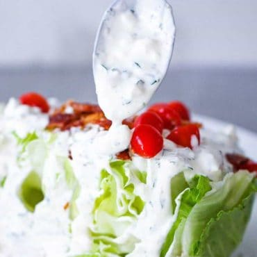 A spoon drizzling homemade blue cheese dressing over a wedge salad.