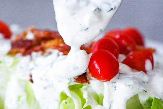 A spoon pouring homemade blue cheese dressing over lettuce with tomatoes and bacon bits.