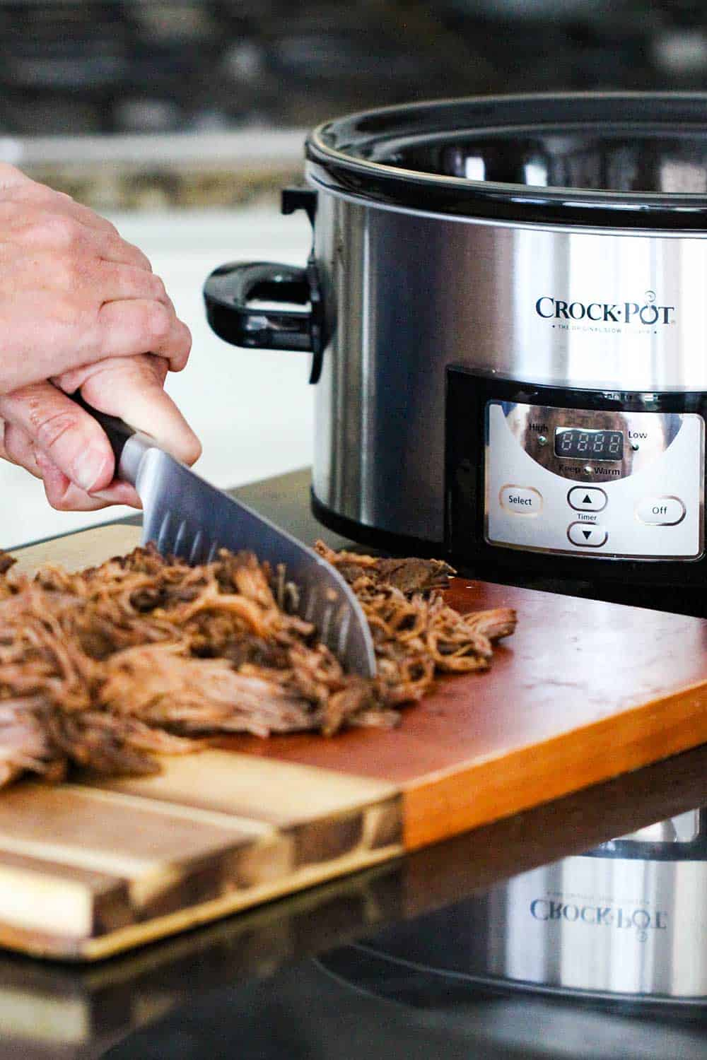 A large knife cutting cooked BBQ brisket next to a silver Crock-Pot.