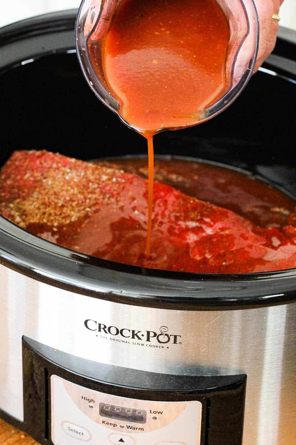 Homemade BBQ sauce being pour over a brisket in a Crock-Pot slow-cooker for BBQ brisket sandwiches.
