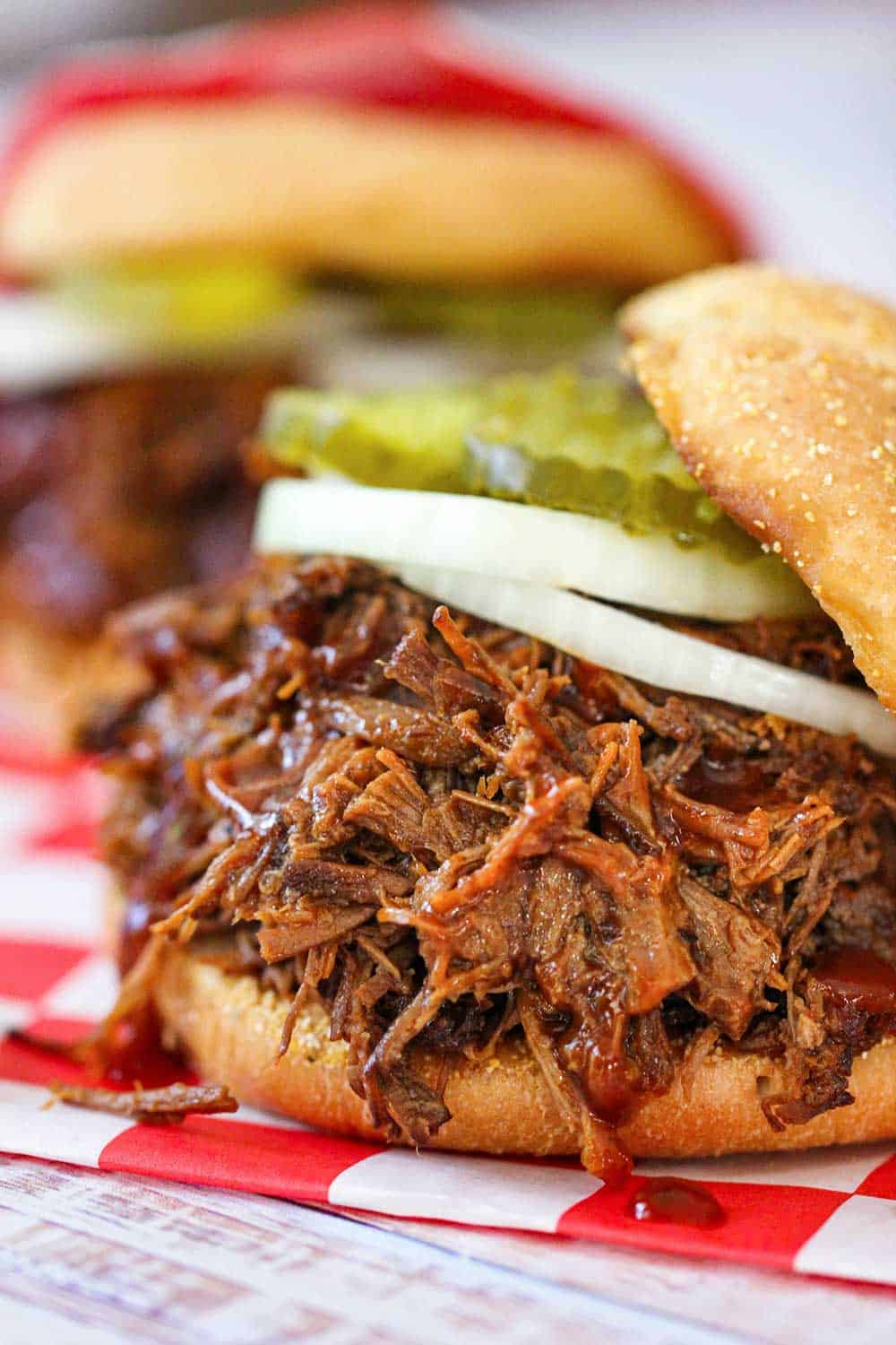 A close-up view of a slow-cooker BBQ brisket sandwich with a sliced onion and pickles on a checkered cloth.