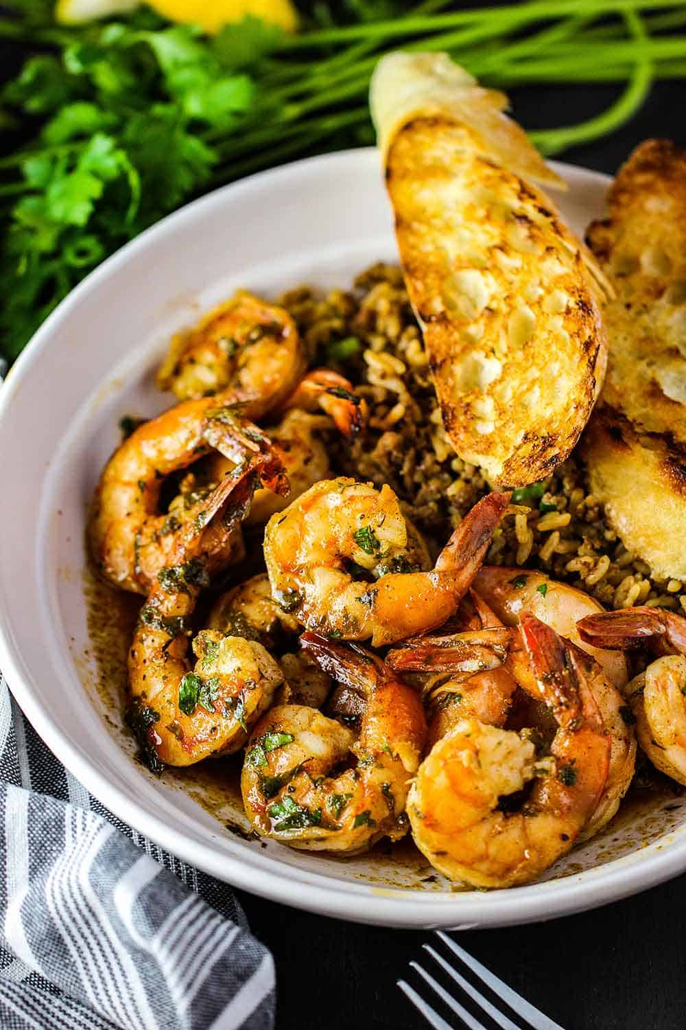 A white bowl containing Cajun bake shrimp, dirty rice and grilled bread.