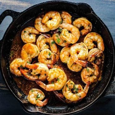 Bake Cajun Baked Shrimp in a black cast iron skillet.