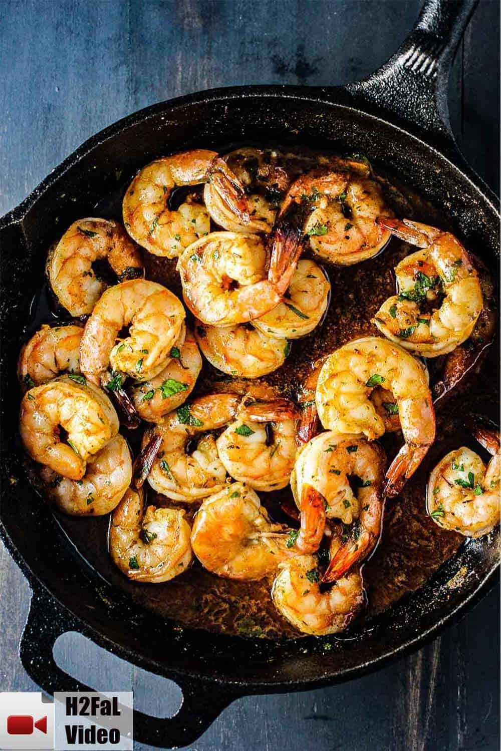 Baked cajun shrimp in a black cast iron skillet.