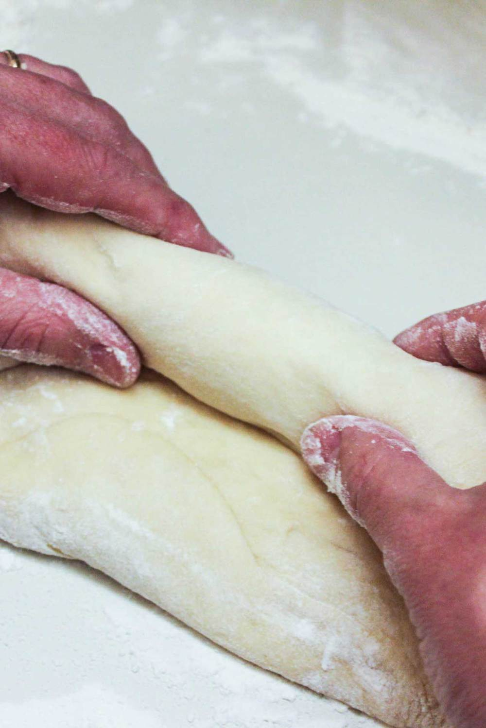 Homemade Country white bread dough being rolled by two hands