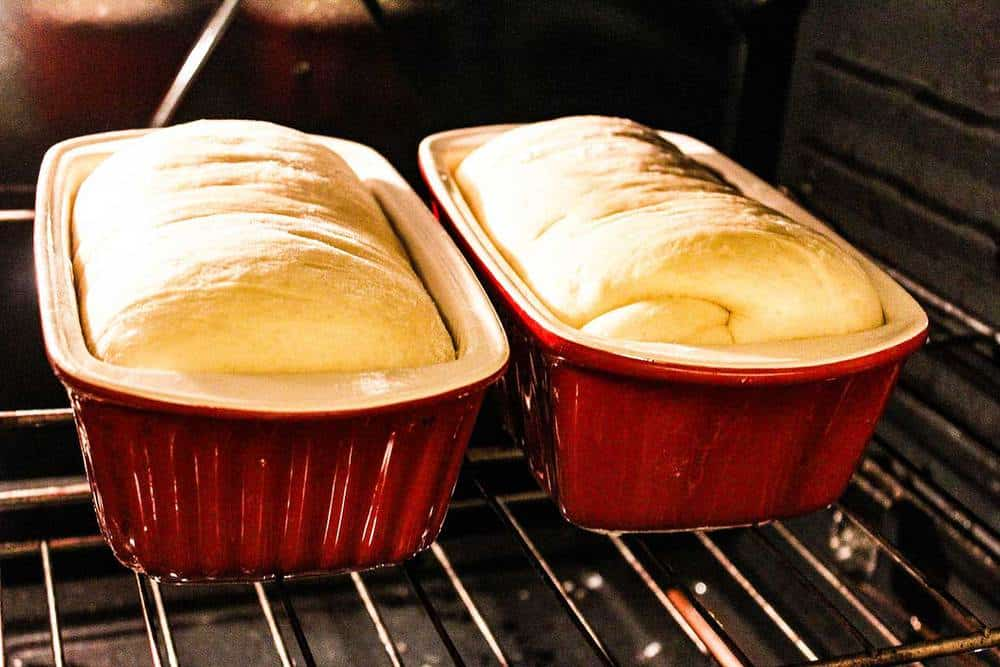 Homemade bread in two loaf pans in the oven