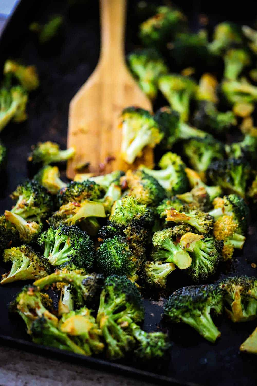 A baking sheet filled with roasted broccoli with a wooden spatula in the middle of the pan.