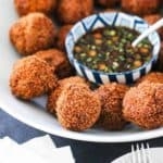 Fried shrimp balls on a platter surround a bowl of spicy dipping sauce.