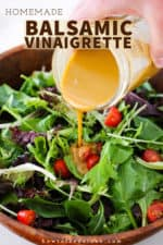 A hand pouring homemade balsamic vinaigrette from a jar onto a bowl filled with a green leaf salad.