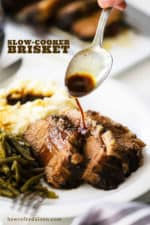 A spoon drizzling au jus sauce on slices of slow cooker brisket on a white plate.