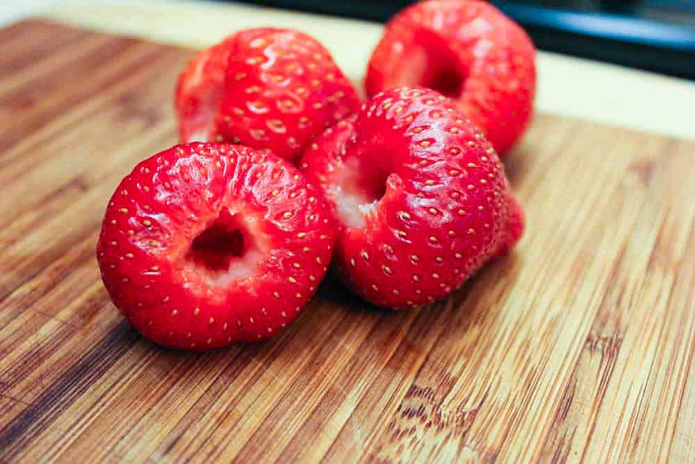 Four fresh strawberries that have been hulled and sitting on a wooden cutting board.