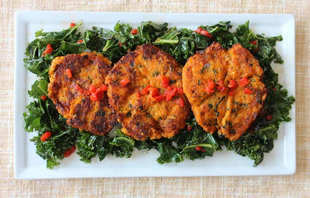 Sweet Potato & Quinoa Cakes with Citrus Kale Salad on a white plate