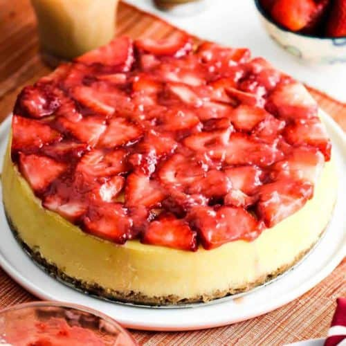 New York Style Cheese Cake with strawberries on top sitting next to a cup of coffee.