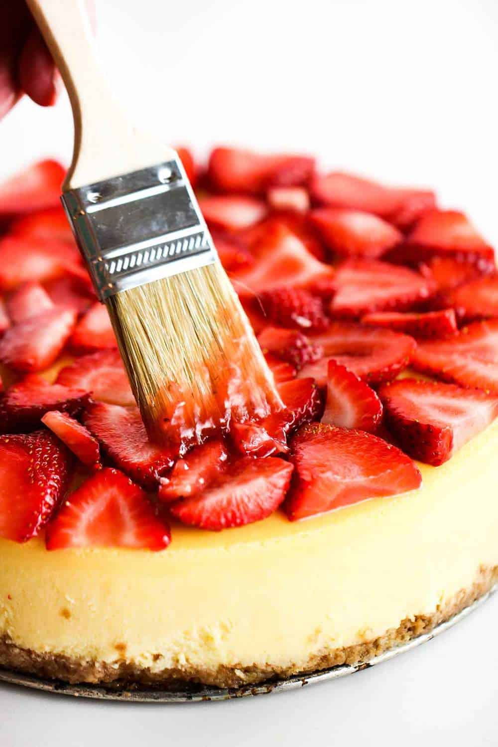 Brush applying a strawberry glaze on top of a New York cheese cake.