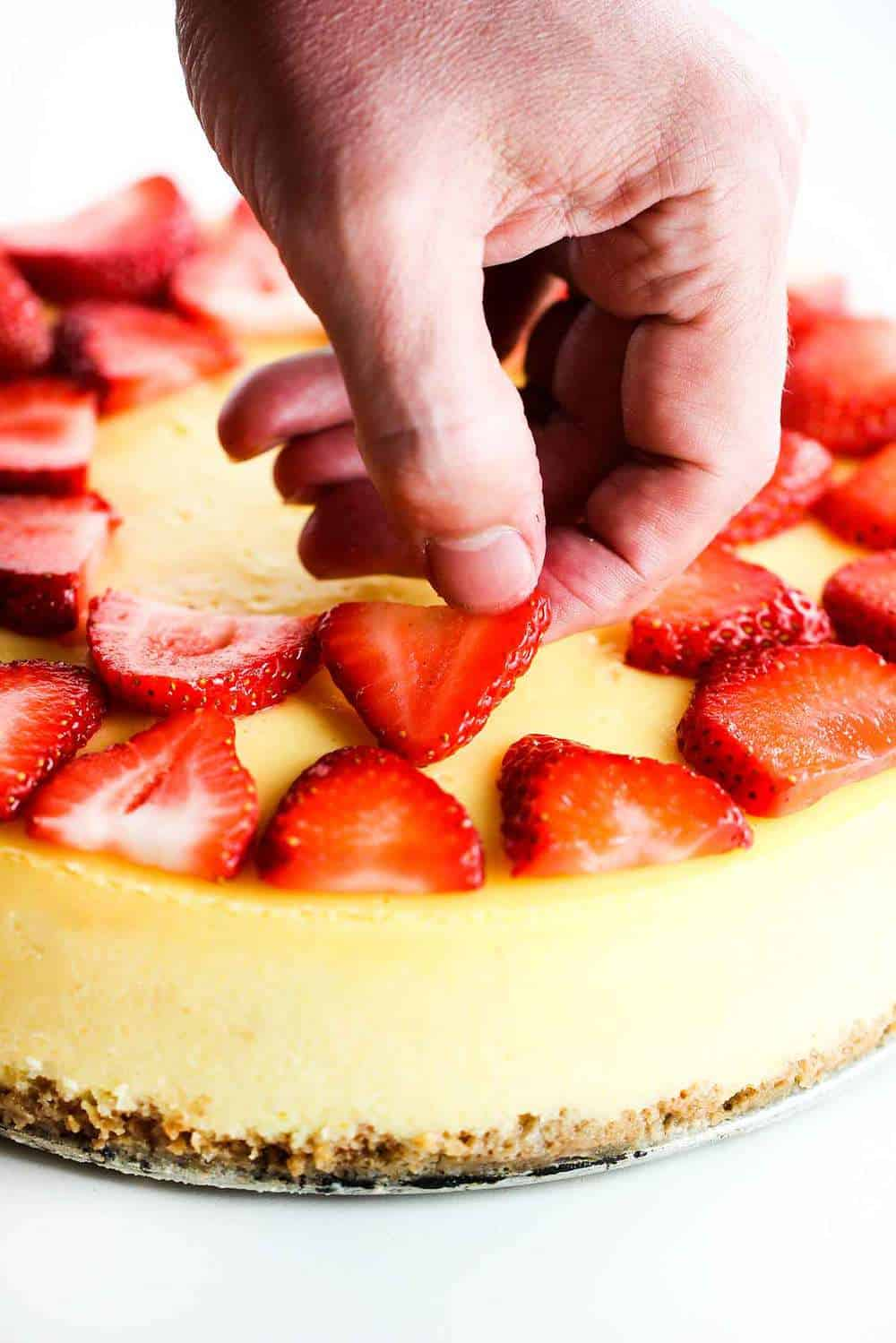 New York Cheese Cake with a hand placing fresh sliced strawberries on top.