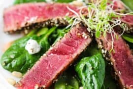 Slices of seared tuna steaks on top of a baby spinach salad.