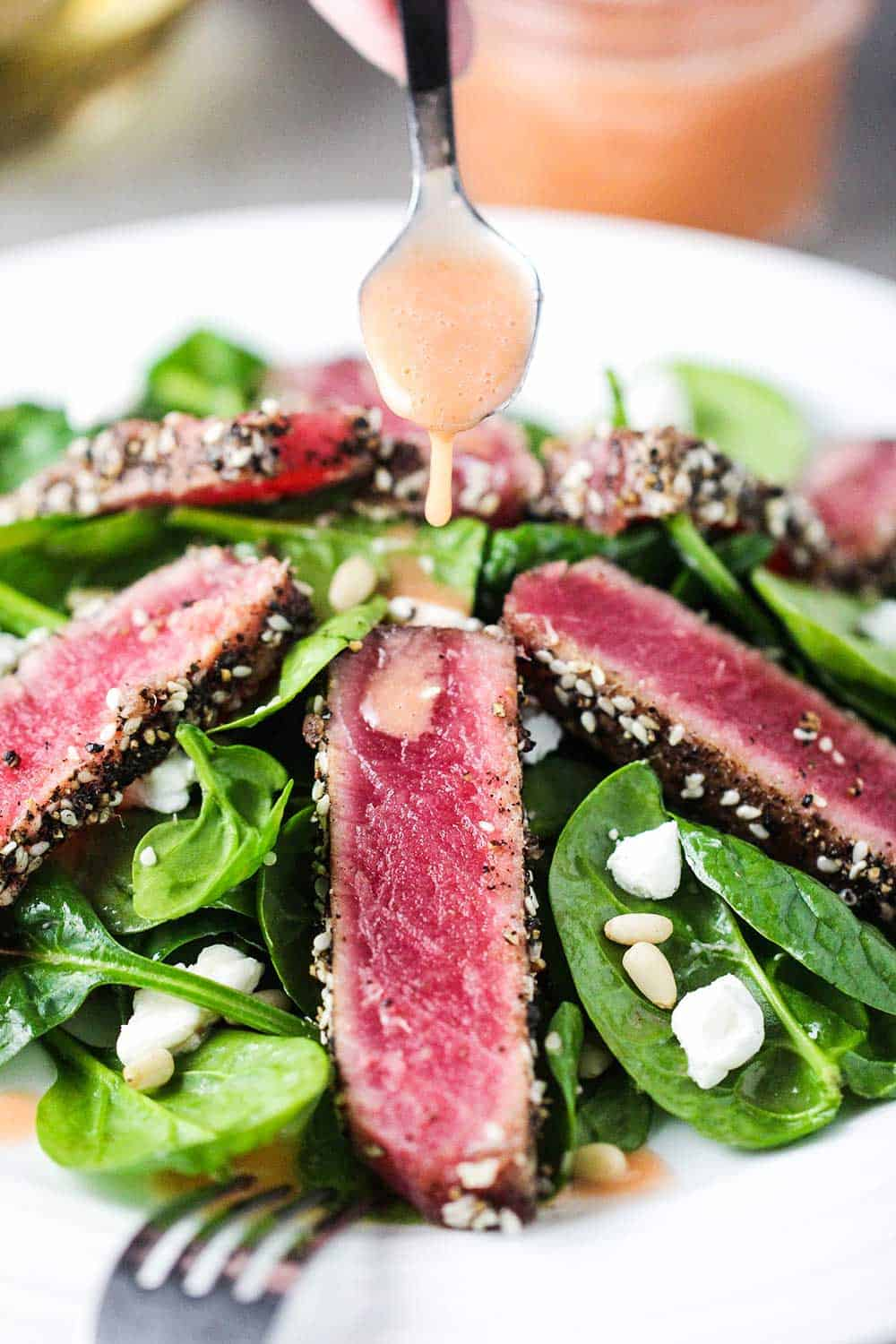 A spoon pouring strawberry vinaigrette over strips of seared tuna steaks on top of a spinach salad on a white plate.