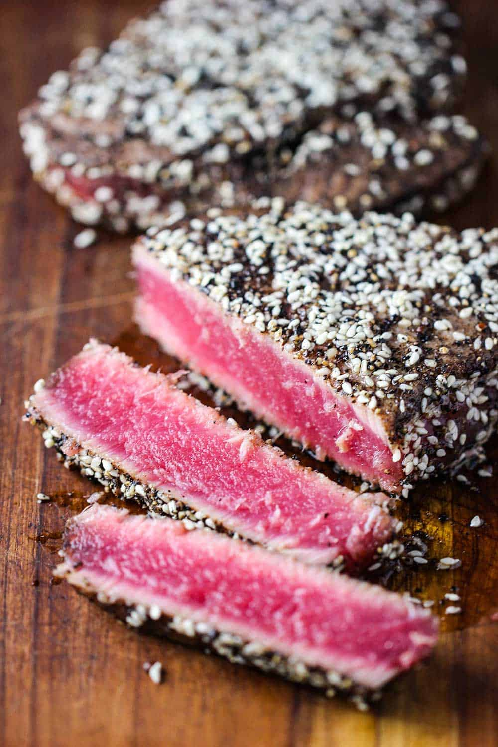 Seared peppercorn tuna steaks the have been sliced on a cutting board with bright pink center.