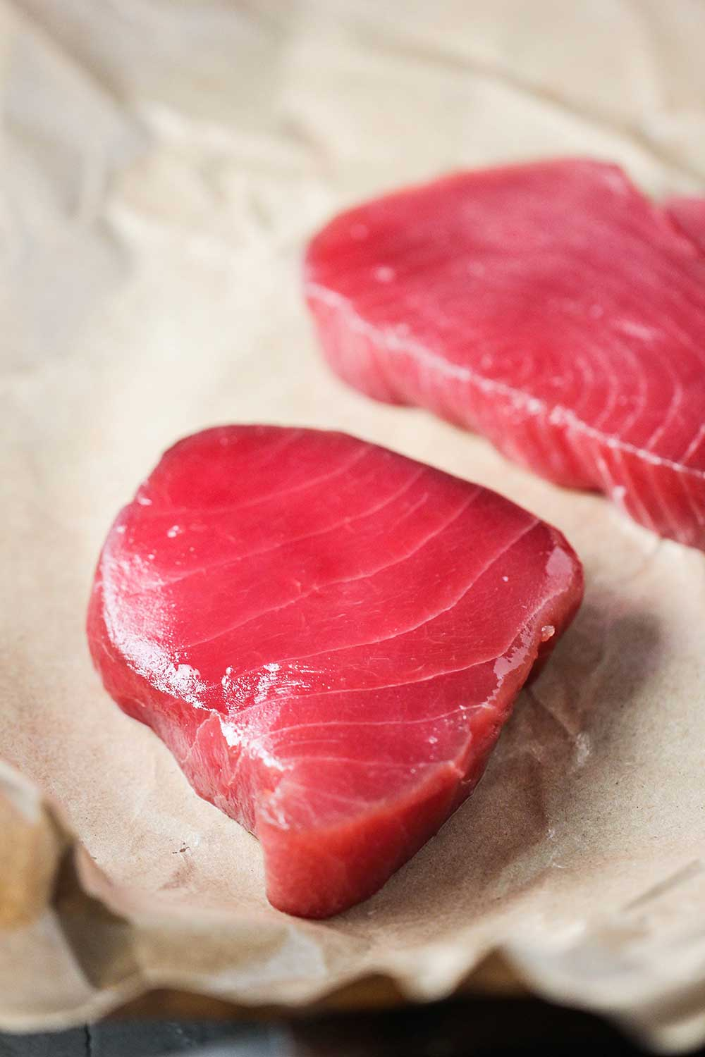 Two vibrant raw tuna steaks on butcher's paper.