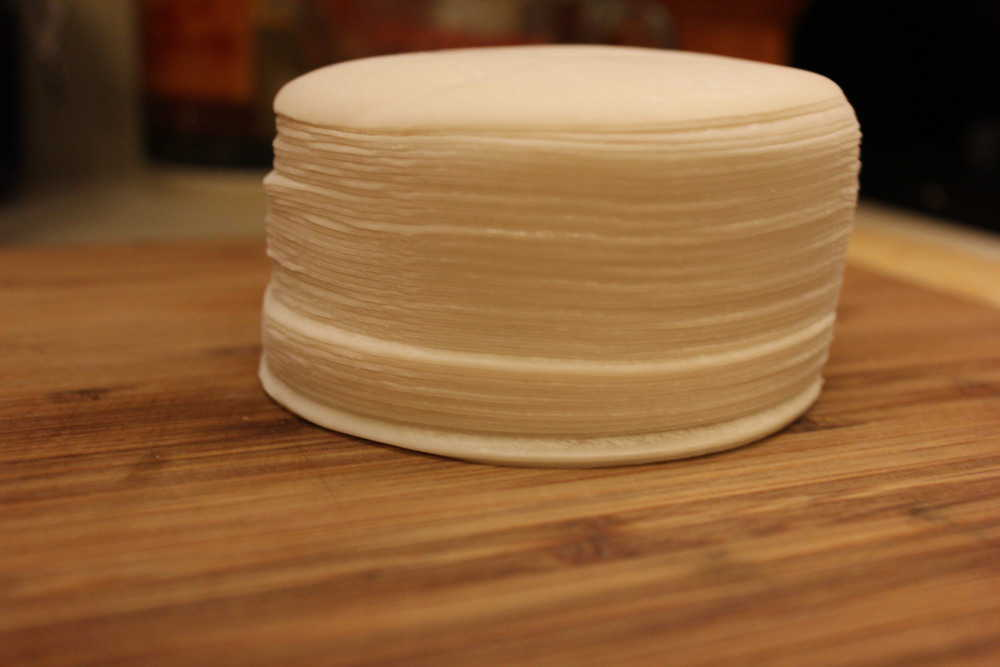 A stack of dumpling skins on a wooden cutting board.