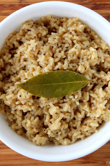 Amazing Cajun rice in a white bowl with a wood background