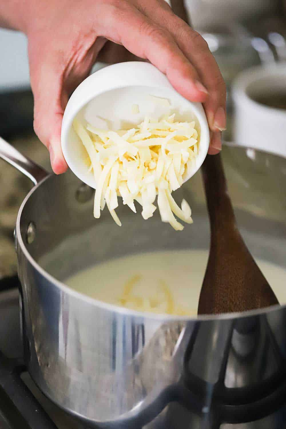 A hand transfer shredded Gruyere cheese from a small white bowl into a sauce pan filled with a béchamel sauce.