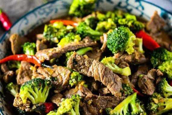 A bowl full of beef and broccoli stir-fry with chop sticks.